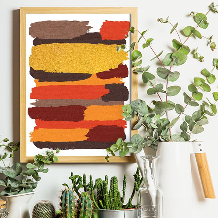 Abstract art print of earthy colored brushstrokes in a wooden frame on wall with succulent plants.