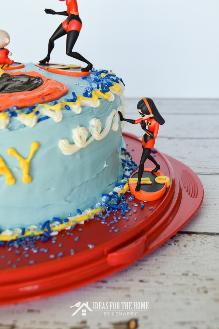 A toy action figure of Violet from The Incredibles appears to creating a force field at the side of a round double layer birthday cake