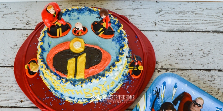 Overhead shot of a round double layer birthday cake with the Incredibles 2 logo and figurines on top