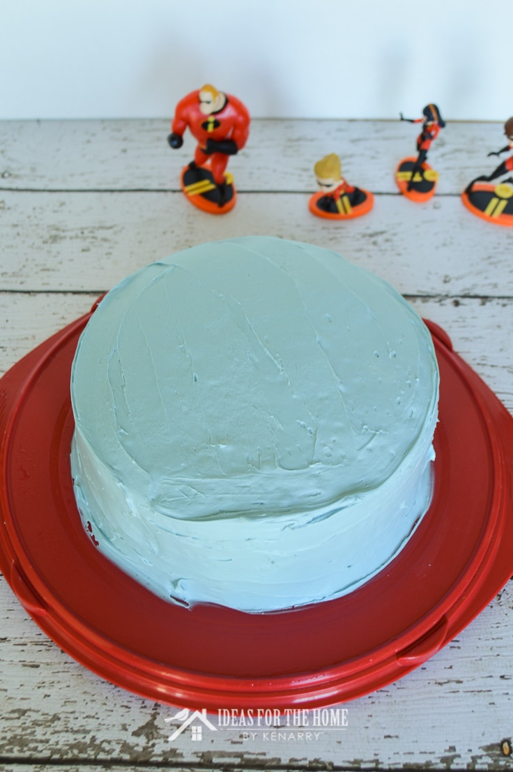 Round double layer cake covered with blue frosting on a cake carrier. Incredibles figurines are in the background.