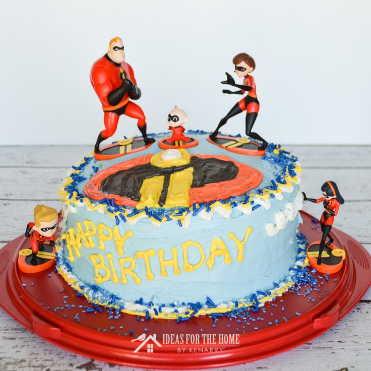 Front view of a round Incredibles birthday cake with figurines of Dash, Violet, Jack Jack, Elastigirl and Mr. Incredible