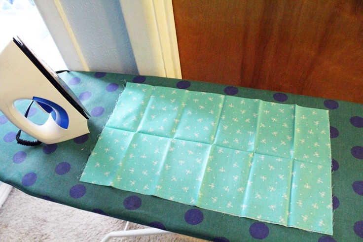 blue fabric on a ironing board beside an iron