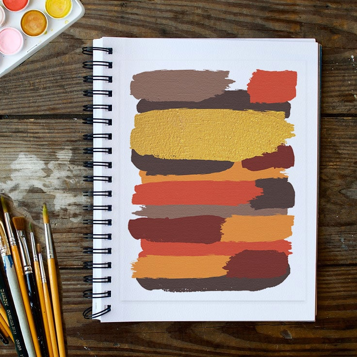 Abstract art print of earthy colored brushstrokes pasted into a spiral bound journal with paints and brushes on the side.