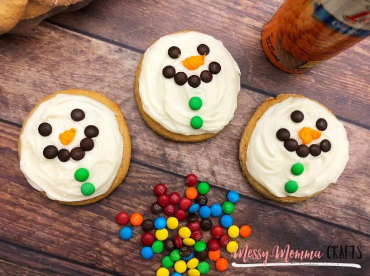 Open the orange can of frosting and attach a circle tip to draw a carrot shaped nose underneath the M&M eyes.