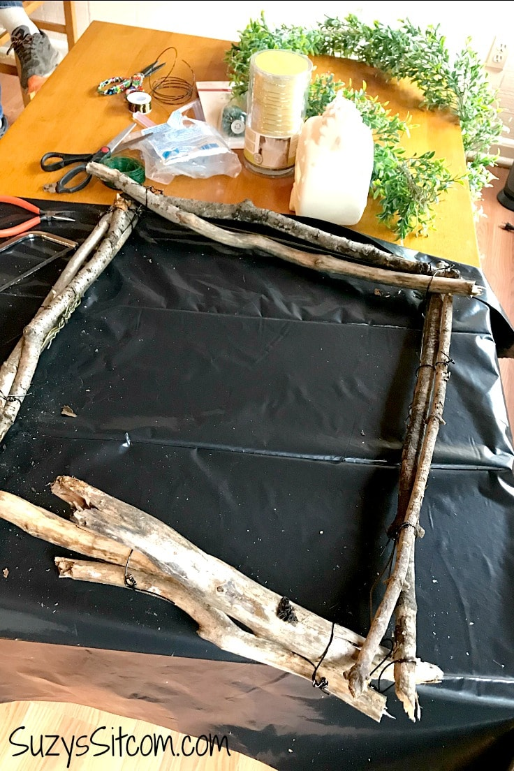Attaching sticks to the wire frame for a rustic wreath