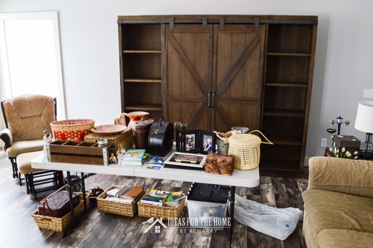 Home decor on a folding table ready to decorate a farmhouse style book case with sliding barn wood doors