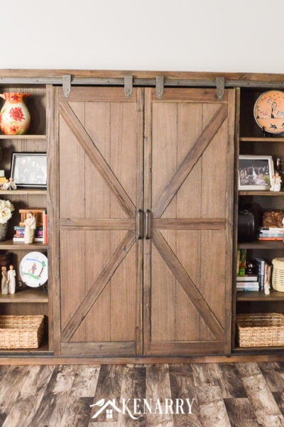 A television is hidden behind sliding barn wood doors on this farmhouse entertainment center.