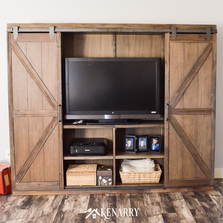 A television can be hidden behind sliding barn wood doors on this farmhouse entertainment center.