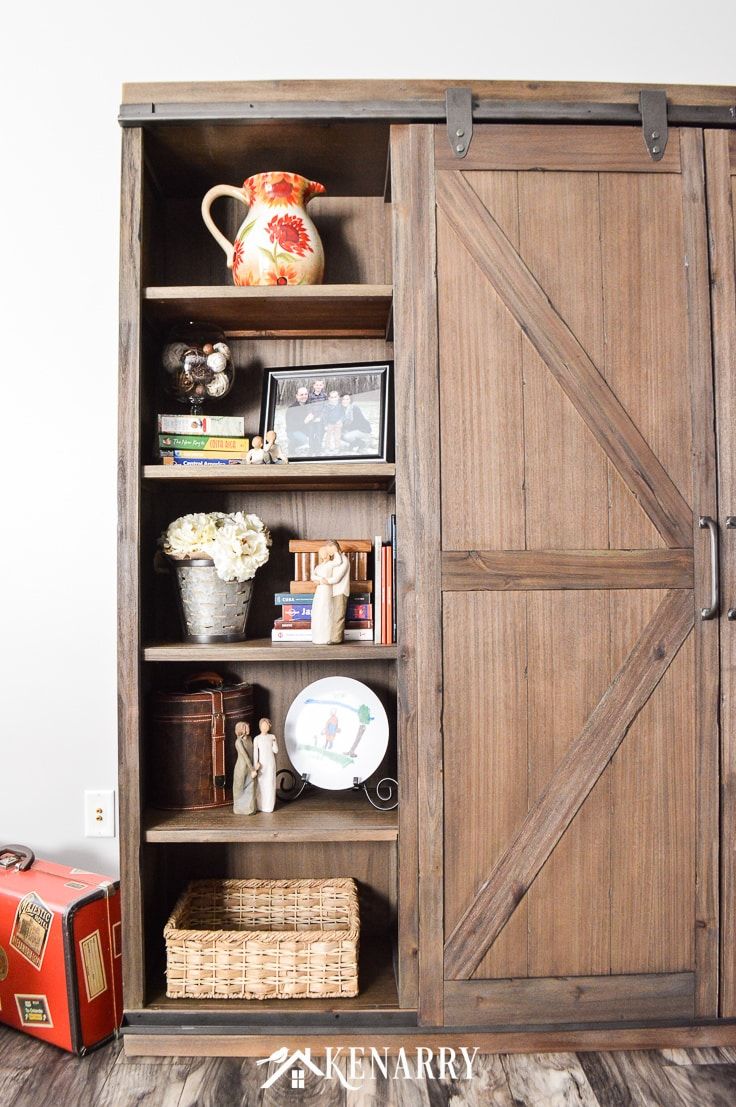 Farmhouse style decor on an entertainment center with sliding barn wood doors