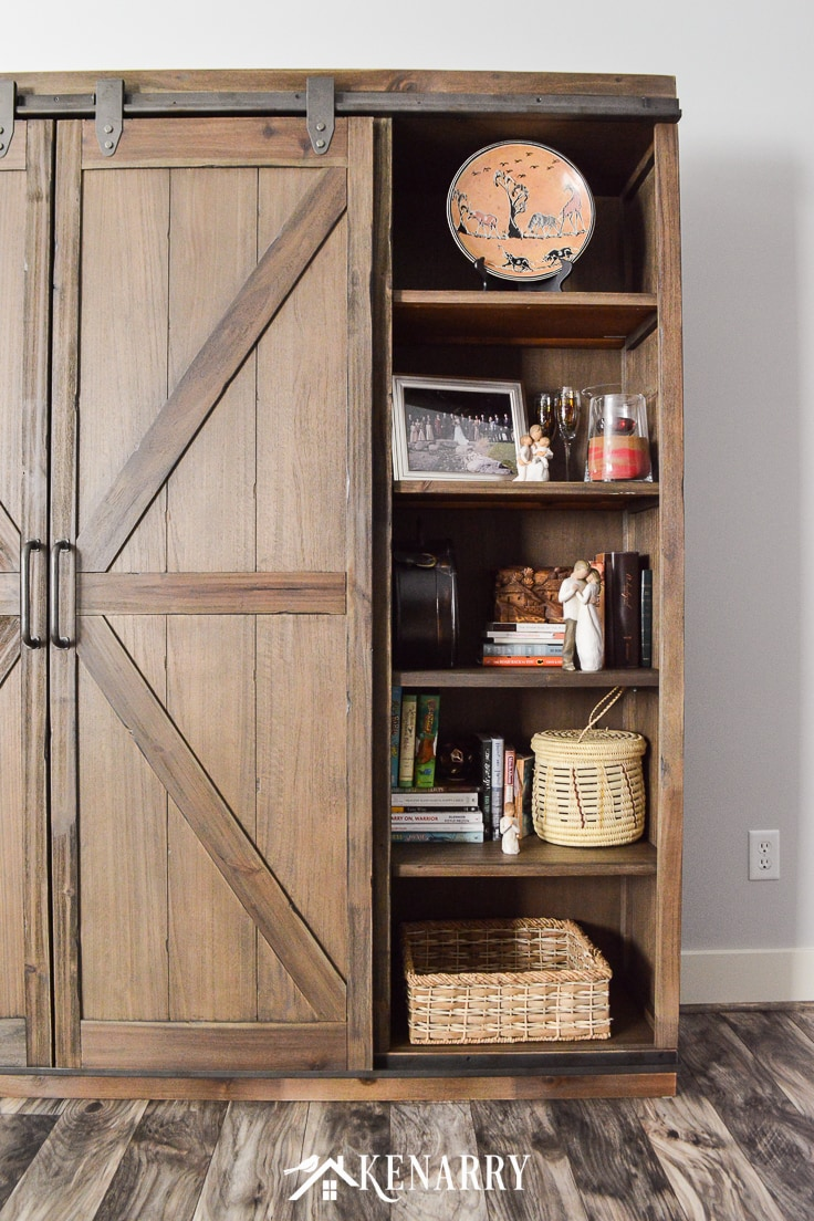 Baskets, Bibles, Willow Tree figurines and other home decor on a bookcase with sliding barn wood doors