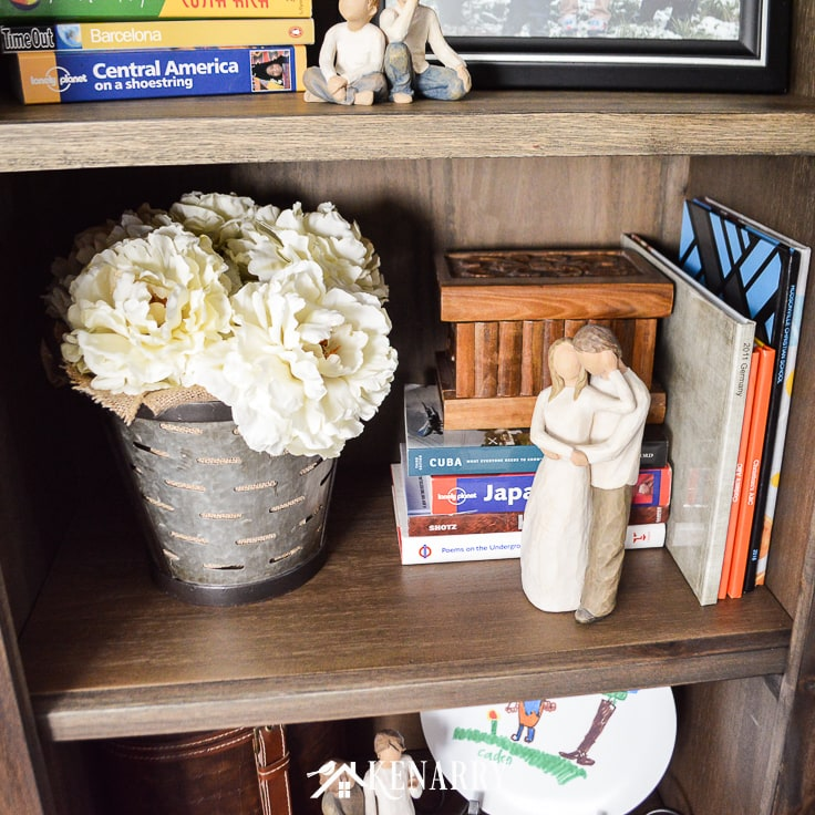 A galvanized metal olive basket filled with burlap and large flowers gives a book shelf farmhouse style