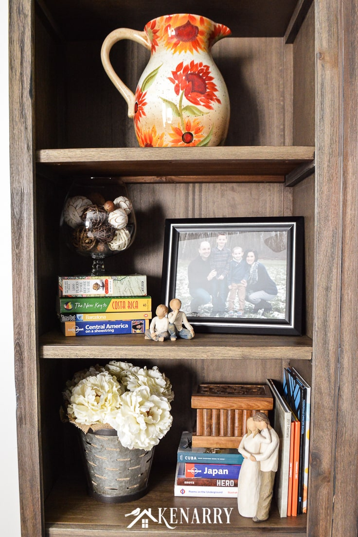 A large farmhouse style pitcher, galvanized metal olive basket filled with flowers, family photo and Willow Tree figurines on a bookshelf