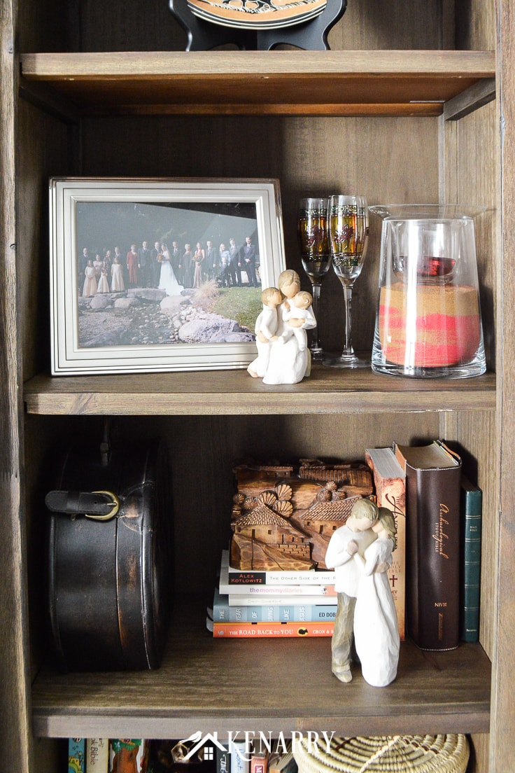 Wedding memorabilia and Willow Tree figurines on a bookshelf