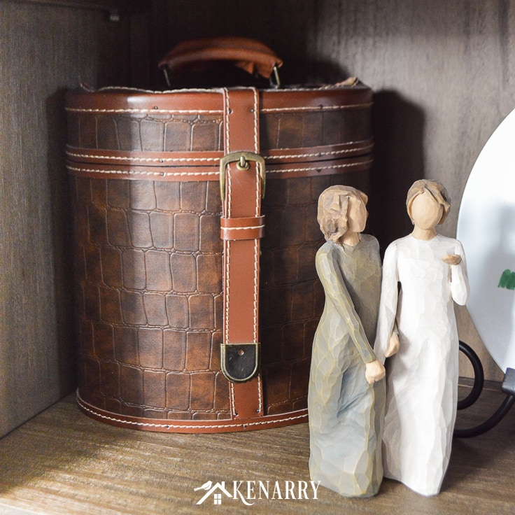 Vintage style leather suitcase with Willow Tree figurine on a shelf