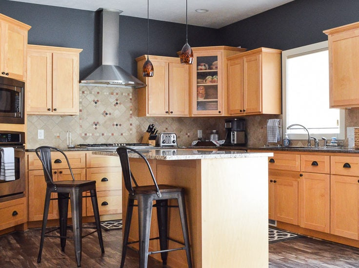 Kitchen reveal showcasing natural maple cabinets and Allen and Roth Chesterfield Hackberry laminate flooring. An industrial style metal bar stool with wood seat next to a kitchen island with Giallo Ornamental granite.