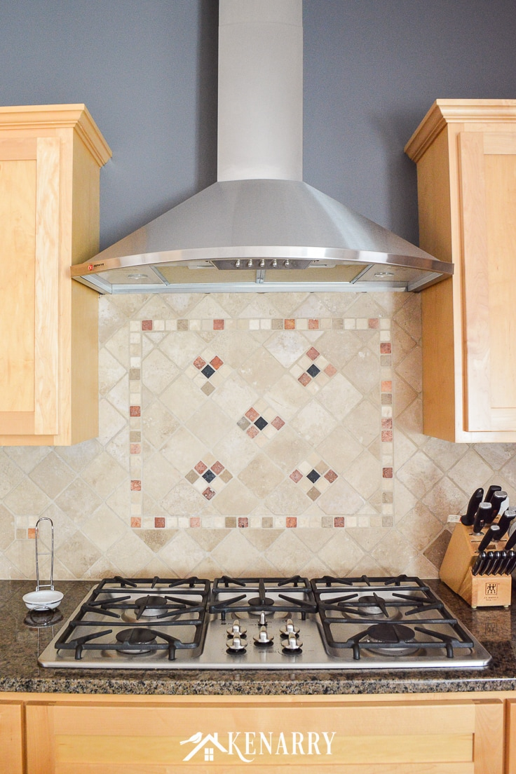 Decorative tile back splash above a built-in stainless steel GE stove top with hood fan