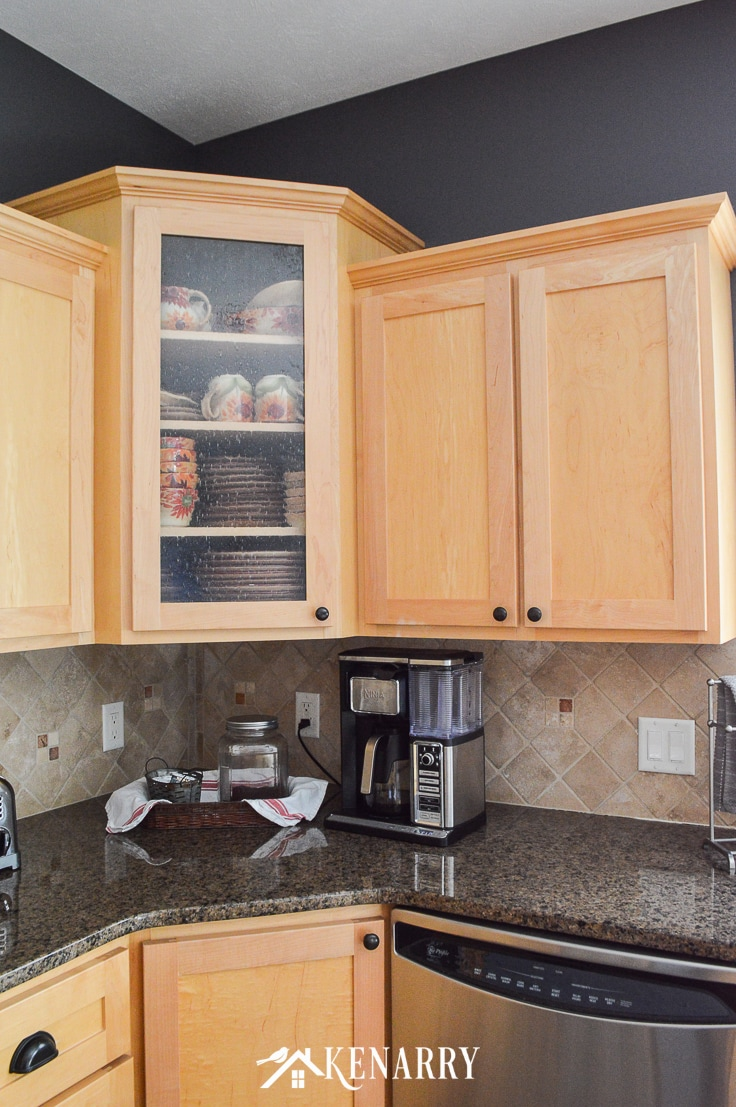 Corner cabinet in a kitchen with seeded glass door, natural maple cabinets, Tropic Brown granite counter, Ninja Coffee Bar