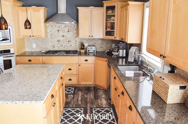 Kitchen with granite counters, natural maple cabinets and tile back splash, shows a sink and built in stove top