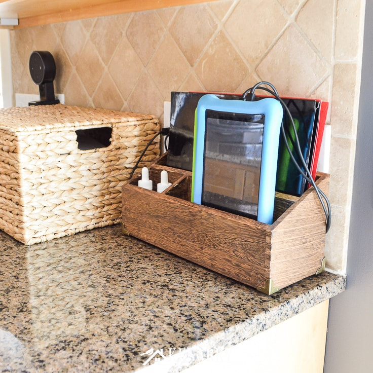 Electronic charging station and wicker basket on a granite counter in a kitchen