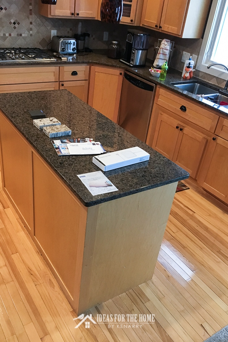 Rectangular kitchen island with granite counter on hickory wood floors