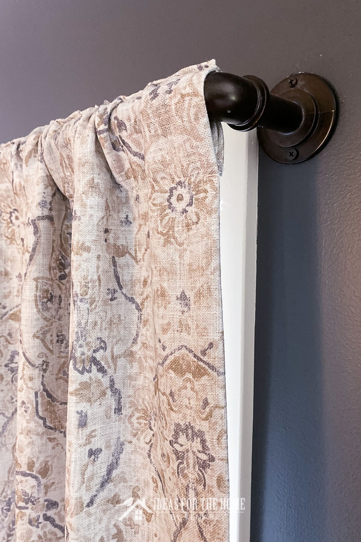 Close up of an industrial metal pipe curtain rod and a gray and tan curtain in a dining room