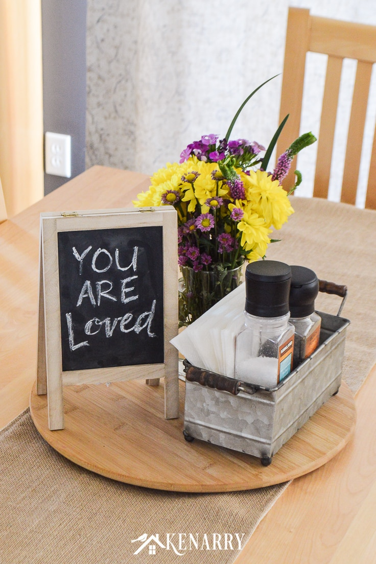 Close up of flowers, a small chalkboard easel, a galvanized metal bin with napkins and salt and pepper grinders on a bamboo lazy susan set on a burlap table runner on top of a natural maple dining room table