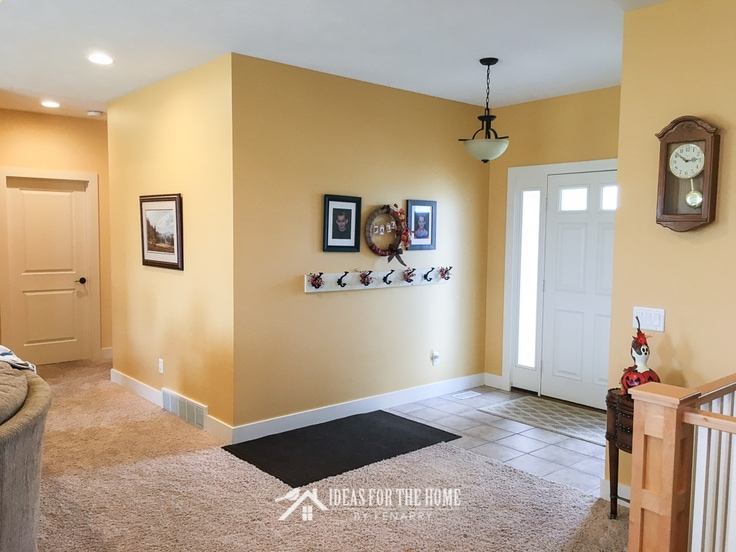 Bright yellow painted entry way with coat hooks - home makeover ideas