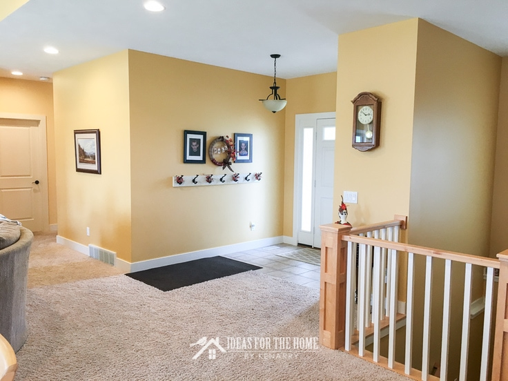 Bright yellow painted entry way with coat hooks next to an open railing