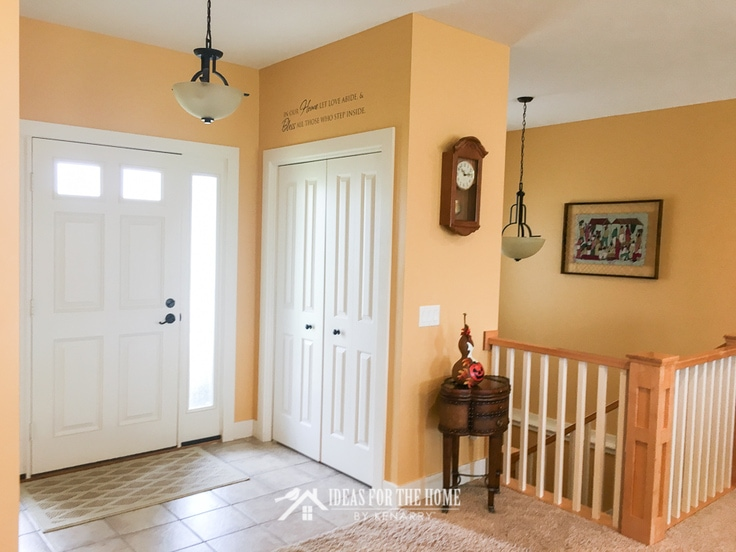 Bright yellow entry way showing the back of a front door and a coat closet. Above the closet it says