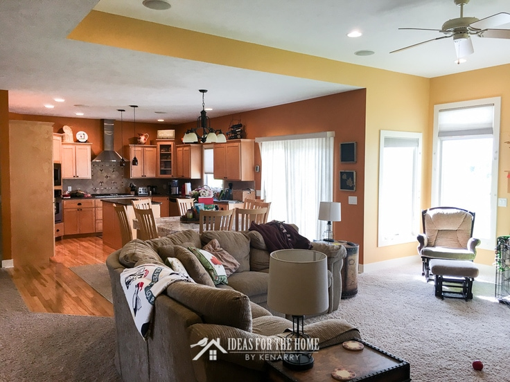 Tan sectional couch in yellow living room adjacent to a rustic orange kitchen with maple cabinets