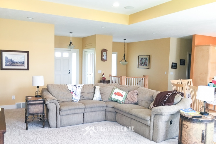 Tan sectional couch in a bright yellow living room