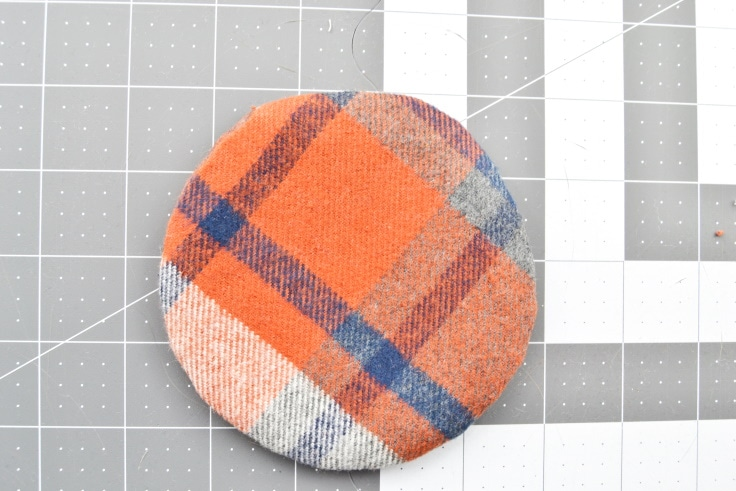 the coaster pressed with the bit of fabric tucked in