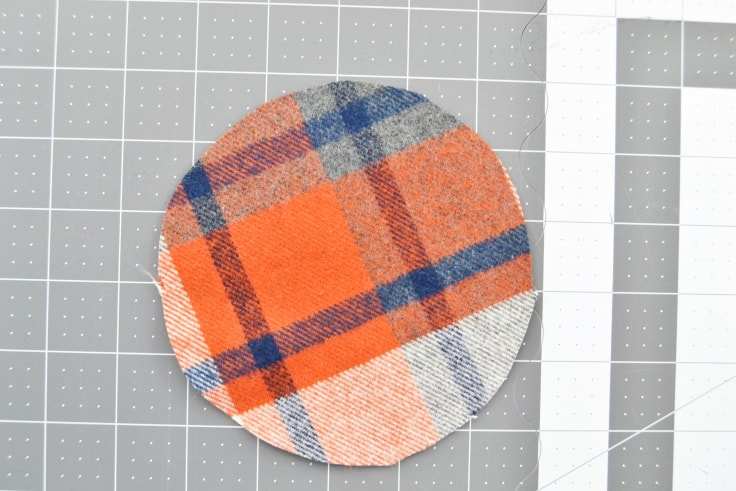 One of the outside fabric circles sitting on the cutting mat with the right side up