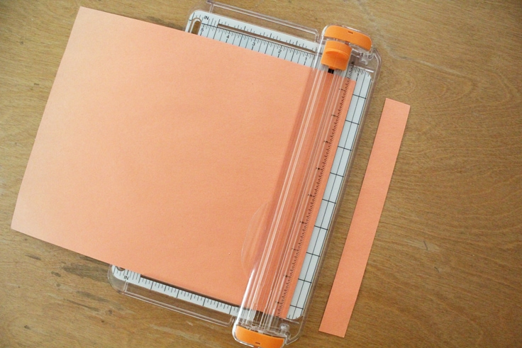 orange construction paper in a wire paper trimmer with a strip cut off one end