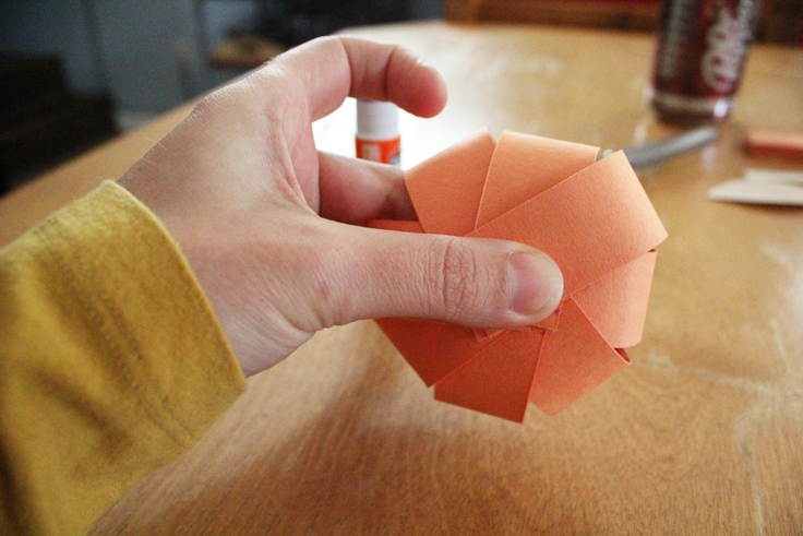 holding the paper sphere while the glue sets