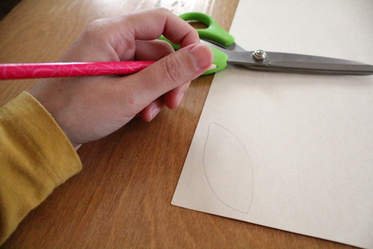 a hand drawing a leaf outline on manila paper