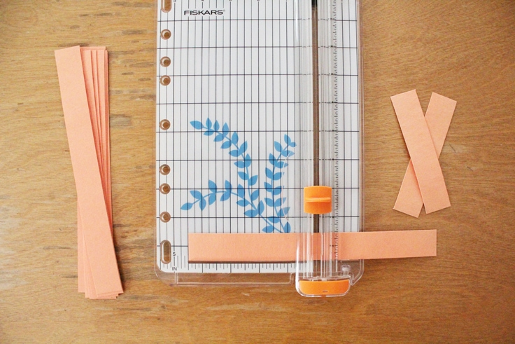 orange paper strips being cut in half with a paper trimmer