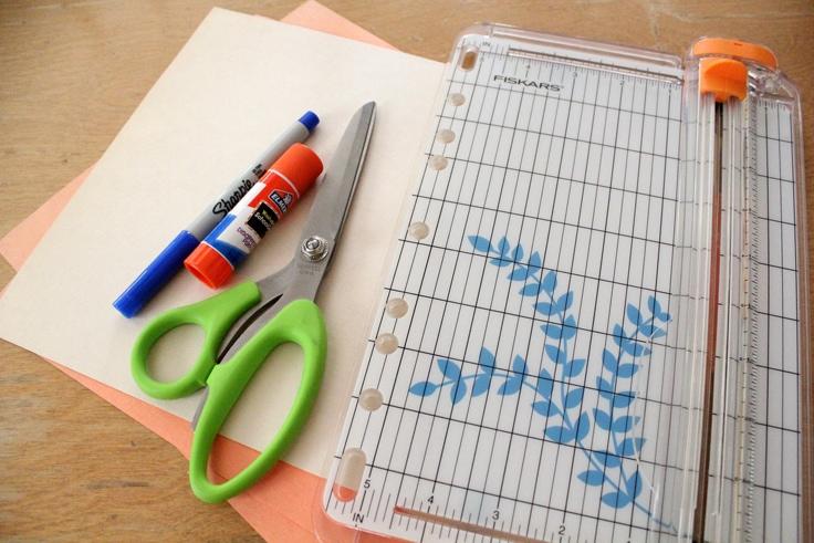 orange and manila construction paper, scissors, a glue stick, a blue Sharpie, and a wire paper trimmer