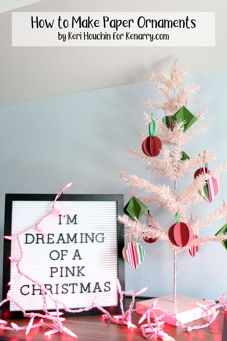 green, red, and pink 3D paper ornaments on a mini pink Christmas tree beside a letterboard that reads