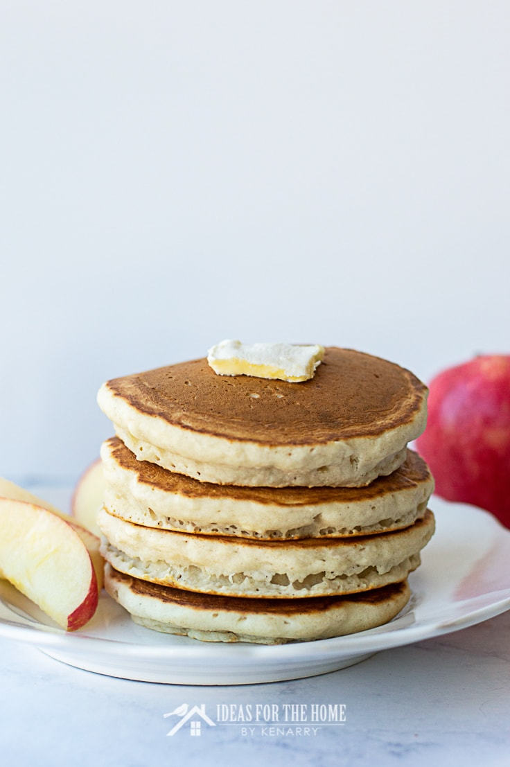 A slab of butter on top of four cinnamon pancakes along with slices of apple