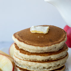 A pitcher of syrup about to be poured on to a stack of cinnamon applesauce pancakes