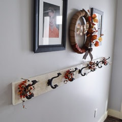 A rustic white farmhouse style coat rack in an entry way with oil rubbed bronze hooks