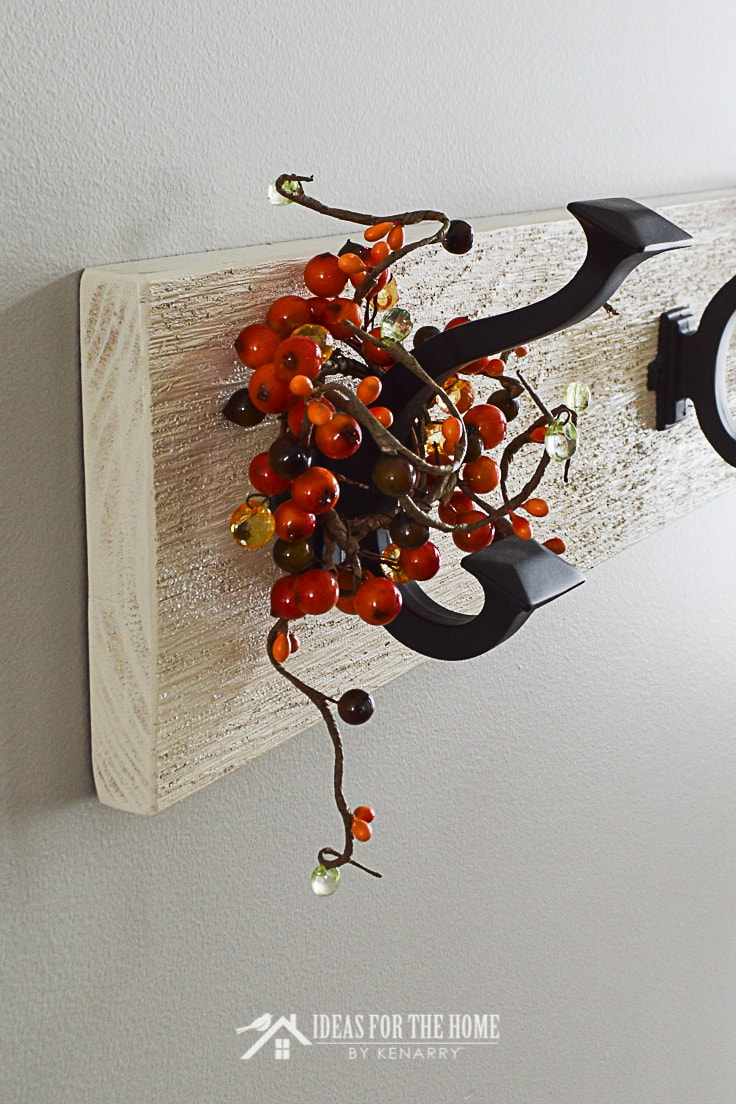 Close up of oil rubbed bronze coat hook on a rustic white rack