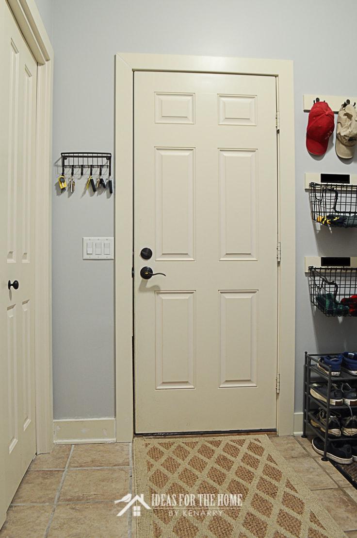 Key organizer next to a garage door in a mudroom