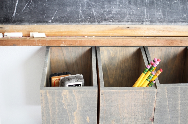 Wooden bin organizer hanging on a wall, holding office and school supplies.