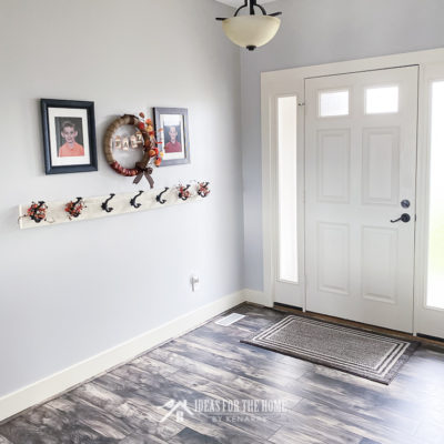 Entry way with laminate wood floors and a farmhouse style coat rack in a home