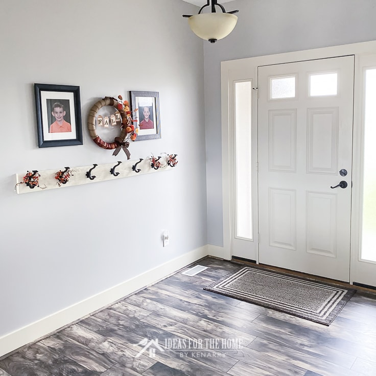 Entryway with laminate wood floors and a farmhouse style coat rack in a home