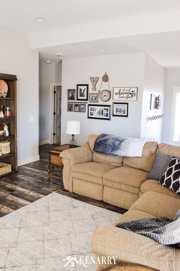 Tan sectional sofa in front of a family photo gallery wall
