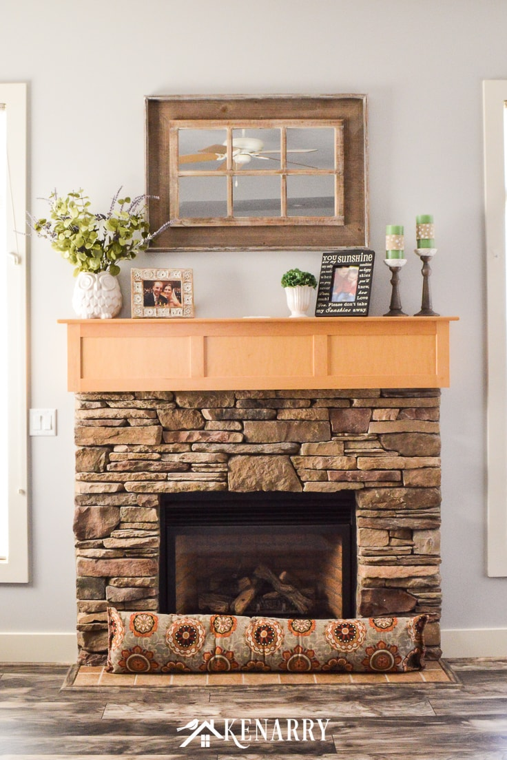 Stone fireplace with natural maple mantel and a rustic wood mirror with farmhouse style