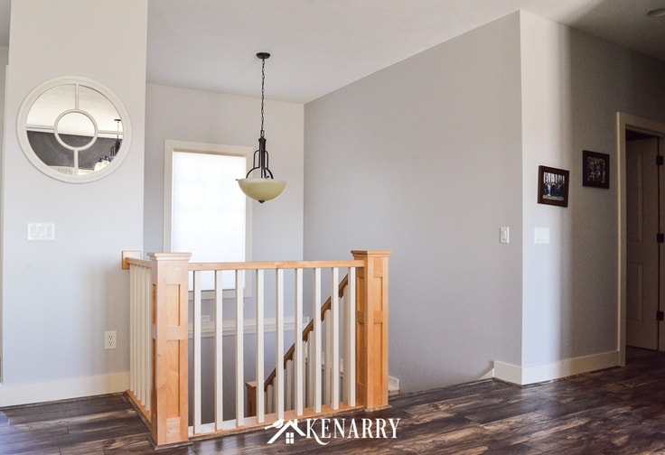 Open concept stairway with natural maple newel posts and white spindles